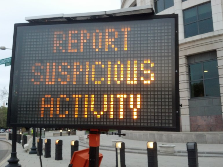 A suspicious activity sign stands in front of the capitol building