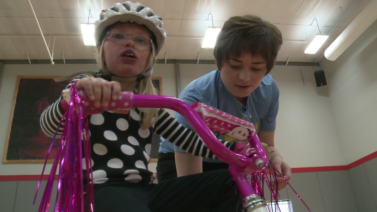 Katie Cook helps Amy Eyles, 9, ride a bike.