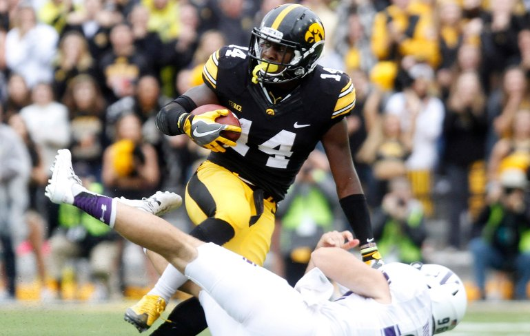 IOWA CITY, IOWA- OCTOBER 1: Defensive back Desmond King #14 of the Iowa Hawkeyes is pulled down during the second quarter by punter Hunter Niswander #96 of the Northwestern Wildcats on October 1, 2016 at Kinnick Stadium in Iowa City, Iowa. (Photo by Matthew Holst/Getty Images)