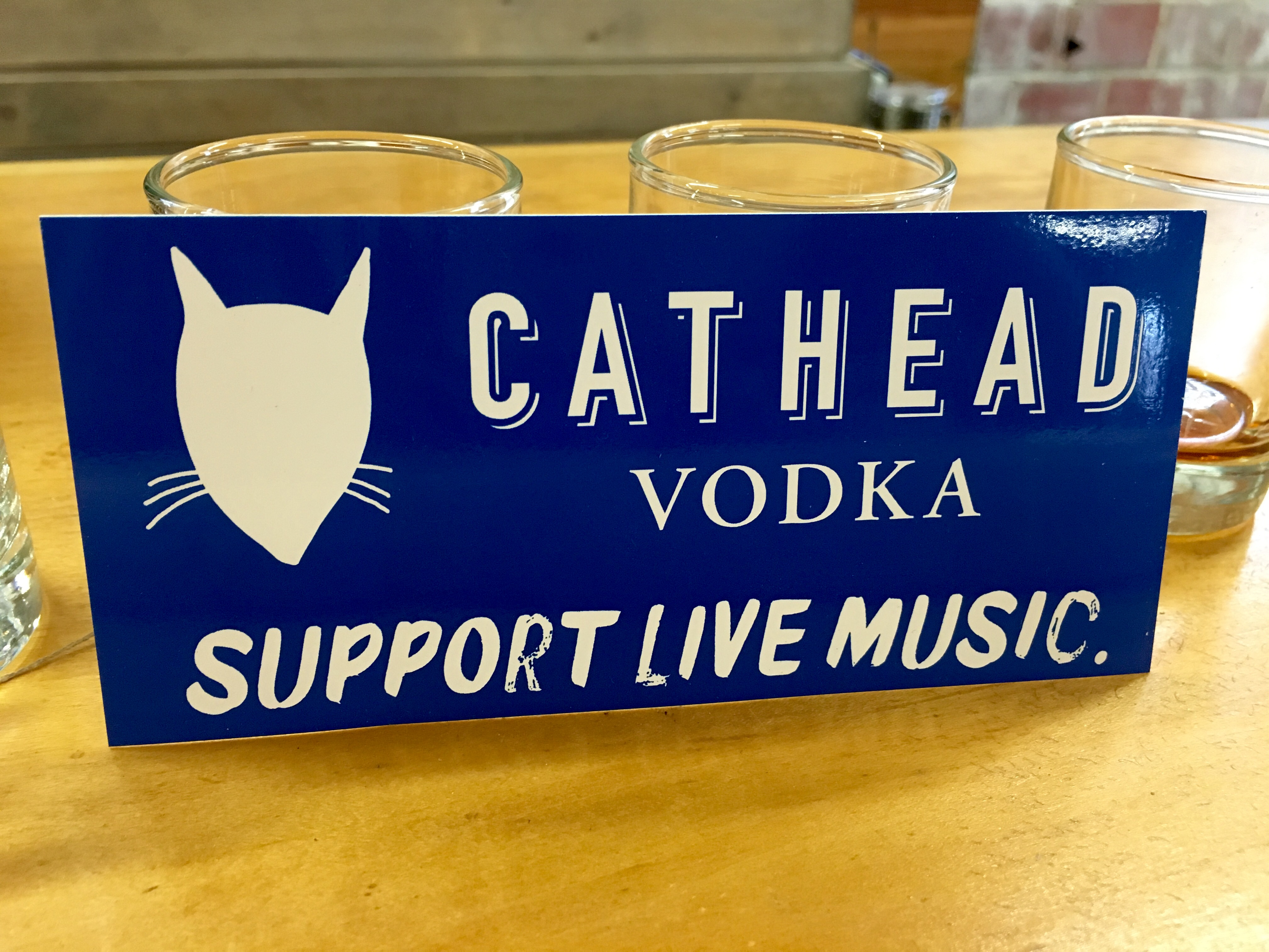 A bumper sticker declares the musical intentions of Cathead Vodka.