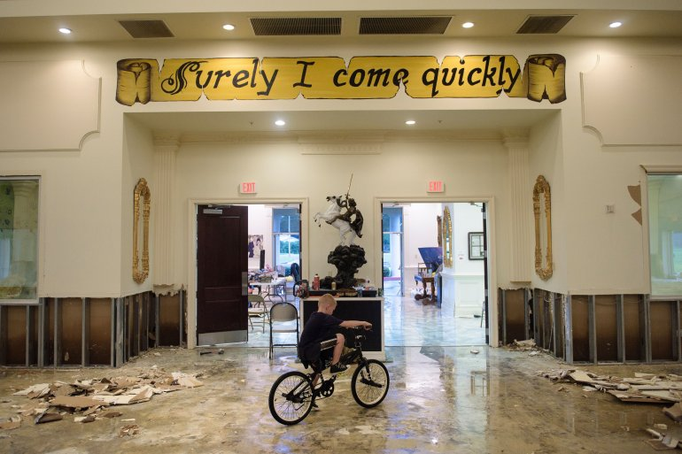 A boy rides his bike inside the flood damaged Life Tabernacle Church on August 15, 2016 in Baton Rouge, Louisiana. Floods ravaged the US state of Louisiana, leaving six people dead and thousands more forced to flee rising waters after days of catastrophic rainstorms.   / AFP / Brendan Smialowski        (Photo credit should read BRENDAN SMIALOWSKI/AFP/Getty Images)