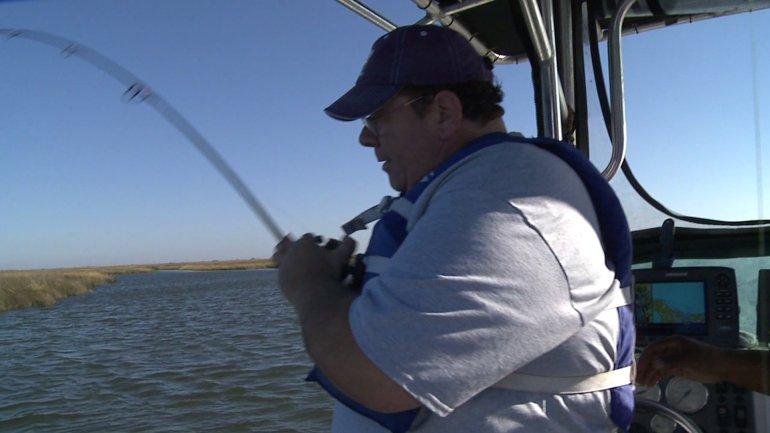 Spud landing a redfish on LBJ's boat (WGNO-TV)