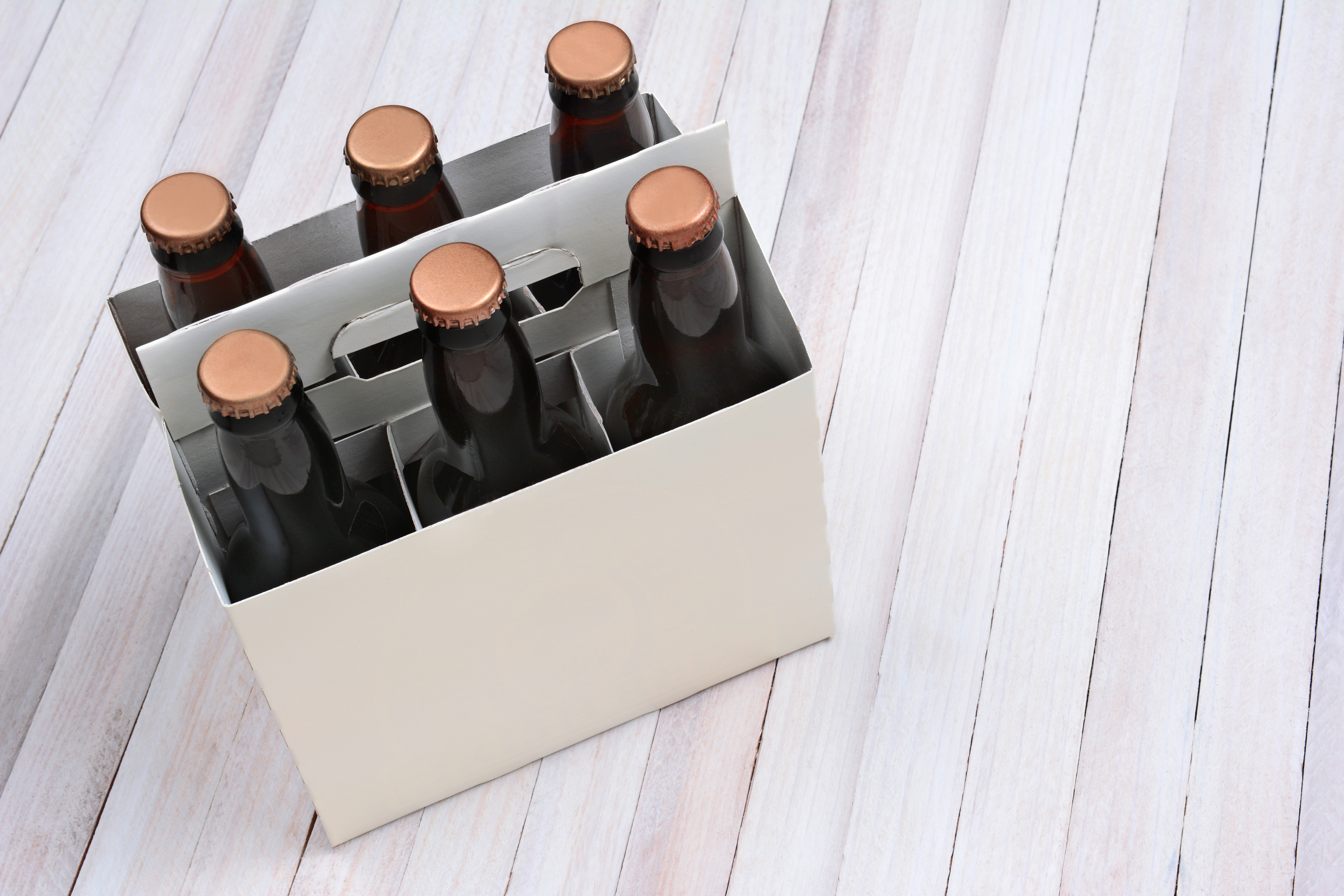 High angle shot of a blank six pack of brown beer bottles on a rustic white wood table. Horizontal format with copy space.