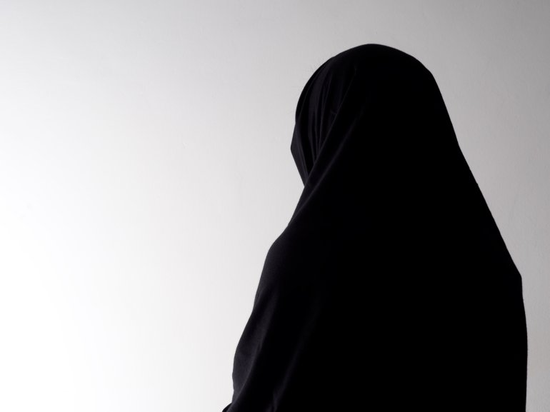 Woman in chador from behind, with copyspace