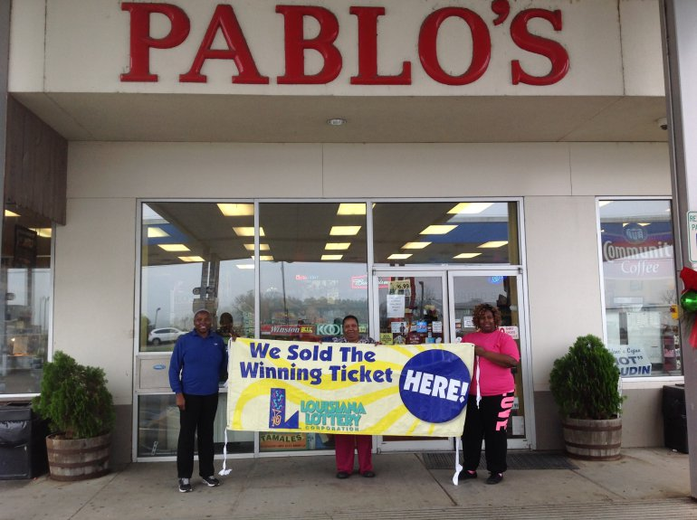 Pablo's cashiers Samantha Joseph, Joan Samuel and Niesha Johnson hold up a Lottery banner in front of their store on Friday, Jan. 8.