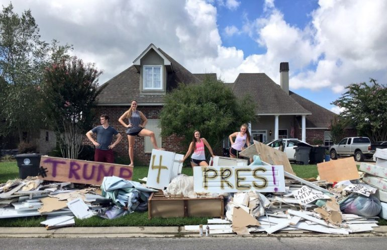 Donald Trump fans show their support outside a flood-ravaged home in the Baton Rouge area.
