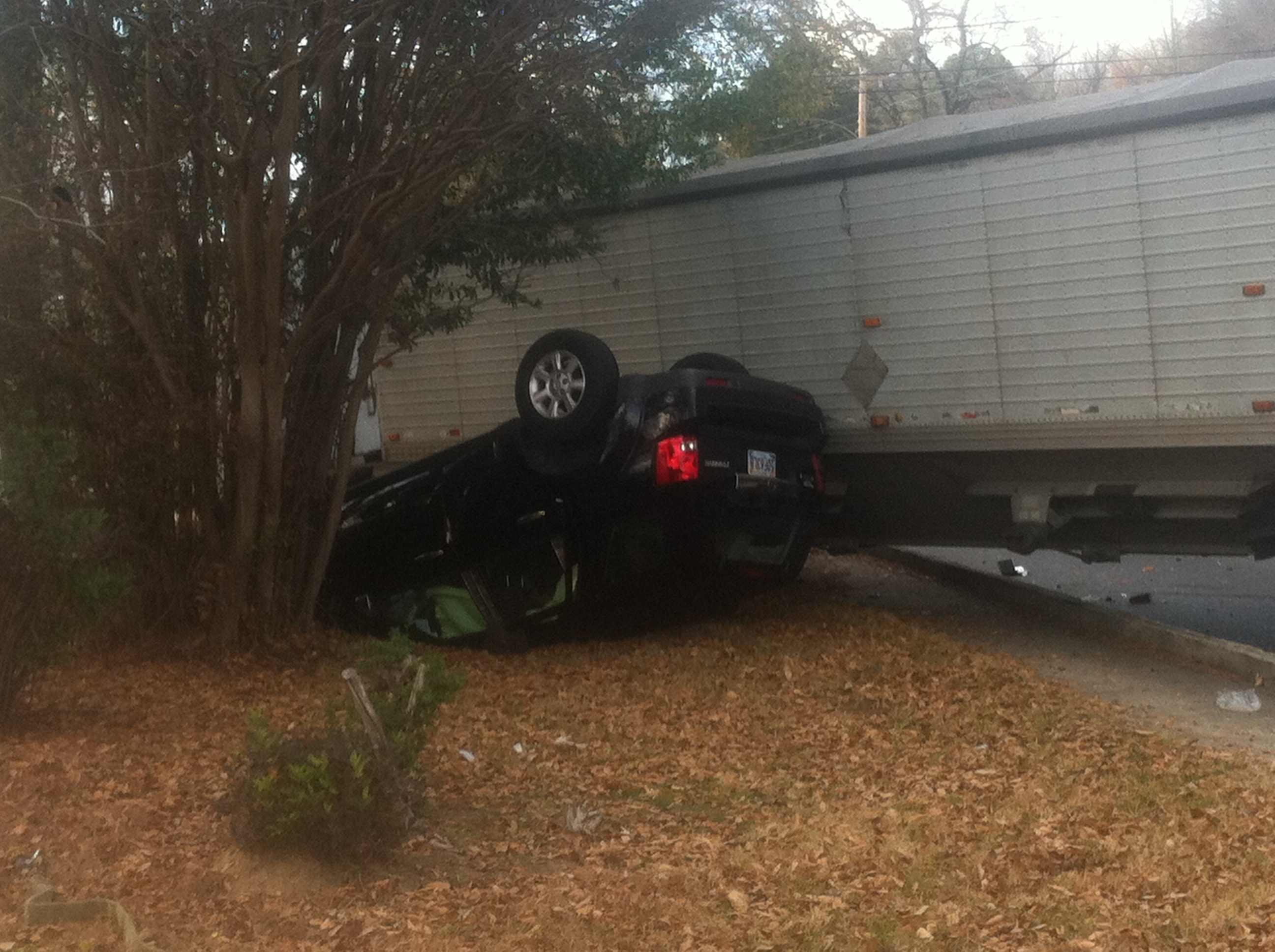 Photo of the black vehicle flipped over, next to the 18-wheeler. (Carson Clark, WHNT News 19)
