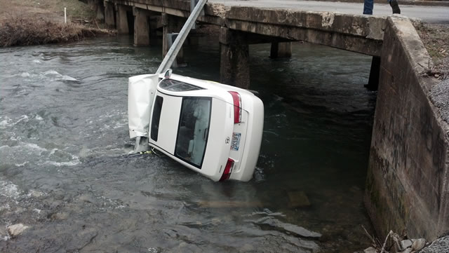 A car went over a guard rail into Cypress Creek on Tuesday morning.  The woman driving was not hurt. (Photo: Carter Watkins/WHNT News 19)