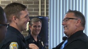 Retired officer David Williams pins his old police badge on his son, Officer Joshua Williams Monday morning. (Photo: Al Whitaker, WHNT News 19)