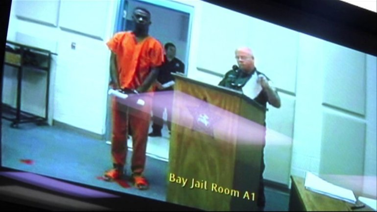 David Daniels, in the orange clothing, appears before a judge via videoconference.