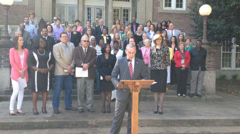 Dr. Casey Wardynski, Superintendent of Huntsville City Schools, discusses the next steps forward. Behind him, the school board, school staff and other community members stand in support of the consent decree. (Photo: Christine Killimayer/WHNT News 19)