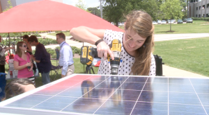 Ivy Elrod helps screw solar panel into roof of cart