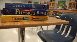 A file photograph showing chemistry, physics and science textbooks sitting on an empty student desk inside an Atlanta, Georgia school. (Ferre' Dollar/CNN)