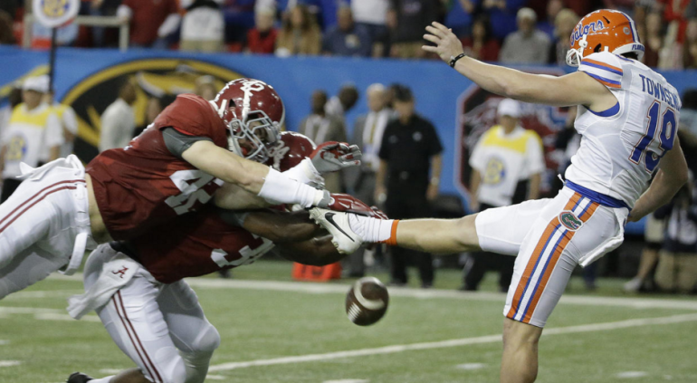 Alabama linebacker Keith Holcombe (42) and Alabama linebacker Christian Miller (34) block the punt of Florida punter Johnny Townsend (19) during the first half of the Southeastern Conference championship NCAA college football game, Saturday, Dec. 5, 2015, in Atlanta. Alabama scored a safety on the play. (AP Photo/David Goldman)