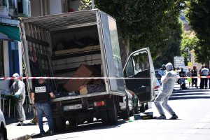 """French police officers search a truck in a street of Nice on July 15, 2016, near the building where the man who drove a truck into a crowd watching a fireworks display the day before reportedly lived. A Tunisian-born man zigzagged a truck through a crowd celebrating Bastille Day in the French city of Nice, killing at least 84 and injuring dozens of children in what President Francois Hollande on July 15 called a """"terrorist"""" attack. / AFP / ANNE-CHRISTINE POUJOULAT (Photo credit should read ANNE-CHRISTINE POUJOULAT/AFP/Getty Images)"""