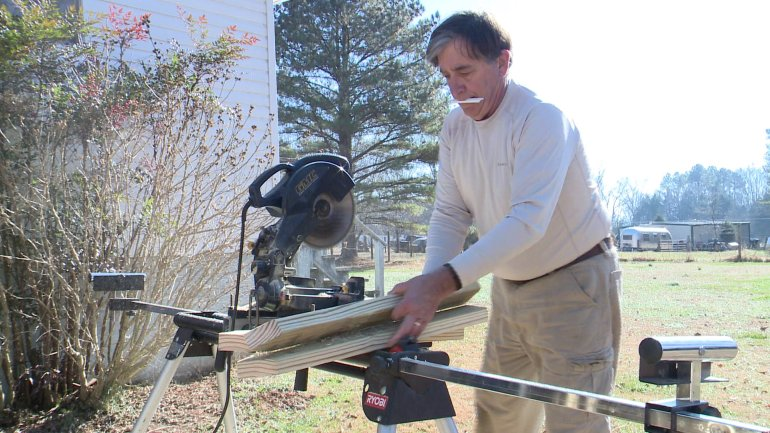 A CASA volunteer saws lumber for a wheelchair ramp.