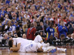 Duke Blue Devils center Jahlil Okafor (15) and Duke Blue Devils guard Tyus Jones (5) embrace after the Blue Devils defeated the Wisconsin Badgers 68-63 in the 2015 NCAA National Championship game Monday, April 6, 2015, at Lucas Oil Stadium.  Matt Detrich/The Star