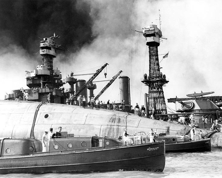 Rescue crews work on the upturned hull of the 29,000 ton battleship USS Oklahoma December 8, 1941. The ship capsized after being blasted by Japanese warplanes December 7, 1941. Holes were burned through the hull to permit the rescue of some of the men trapped below. Credit:Library of Congress Source: US Navy