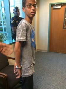 A photo shows Ahmed, wearing a NASA t-shirt, looking confused and upset as he's being led out of school in handcuffs. Credit:Mohamed Family