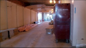 Crews have knocked out old office walls to restore wider hallways with arched ceilings.