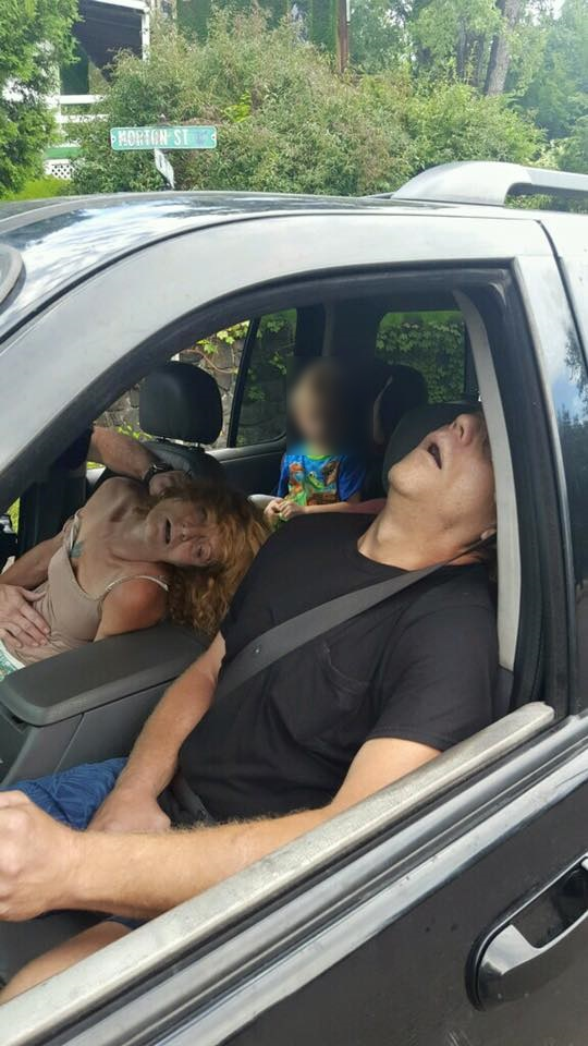 The Liverpool Police Department posted shocking photos to Facebook showing two adults, who police believe were on heroin, passed out in a car with a little boy in the backseat. (Photo Credit: East Liverpool Police)