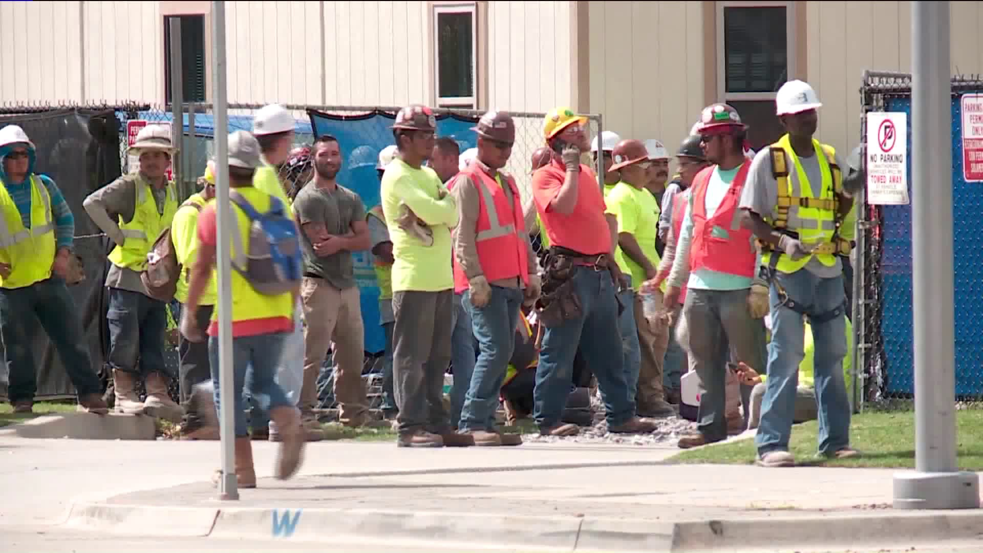 Construction workers gathered outside of work zone after scissor lift operator dies