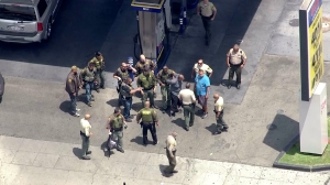 Authorities swarmed a Huntington Park gas station on June 27, 2014, taking a man into custody. (Credit: KTLA)