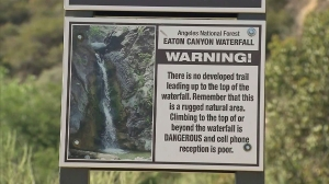 A sign warns hikers of the dangers of the upper falls in Eaton Canyon on June 27, 2014. The Forest Service was expected to close access to the upper falls. (Credit: KTLA)