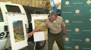 Sheriff Geoff Dean points to photos of the location where Mike Herdman's body was found June 27, 2014. (Credit: KTLA)