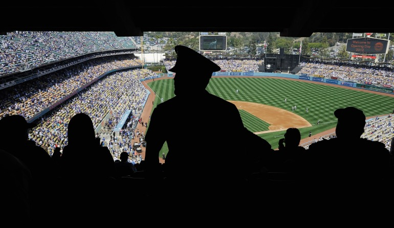 A Los Angeles Police Department officer looks at fans inside Dodger Stadium during the home opener against the Pittsburgh Pirates on April 10, 2012 in Los Angeles, California. Security was high at the stadium for the home opener after Bryan Stow was beaten into a coma in a Dodger Stadium parking lot following the home opener in March of 2011. (Credit: Kevork Djansezian/Getty Images)