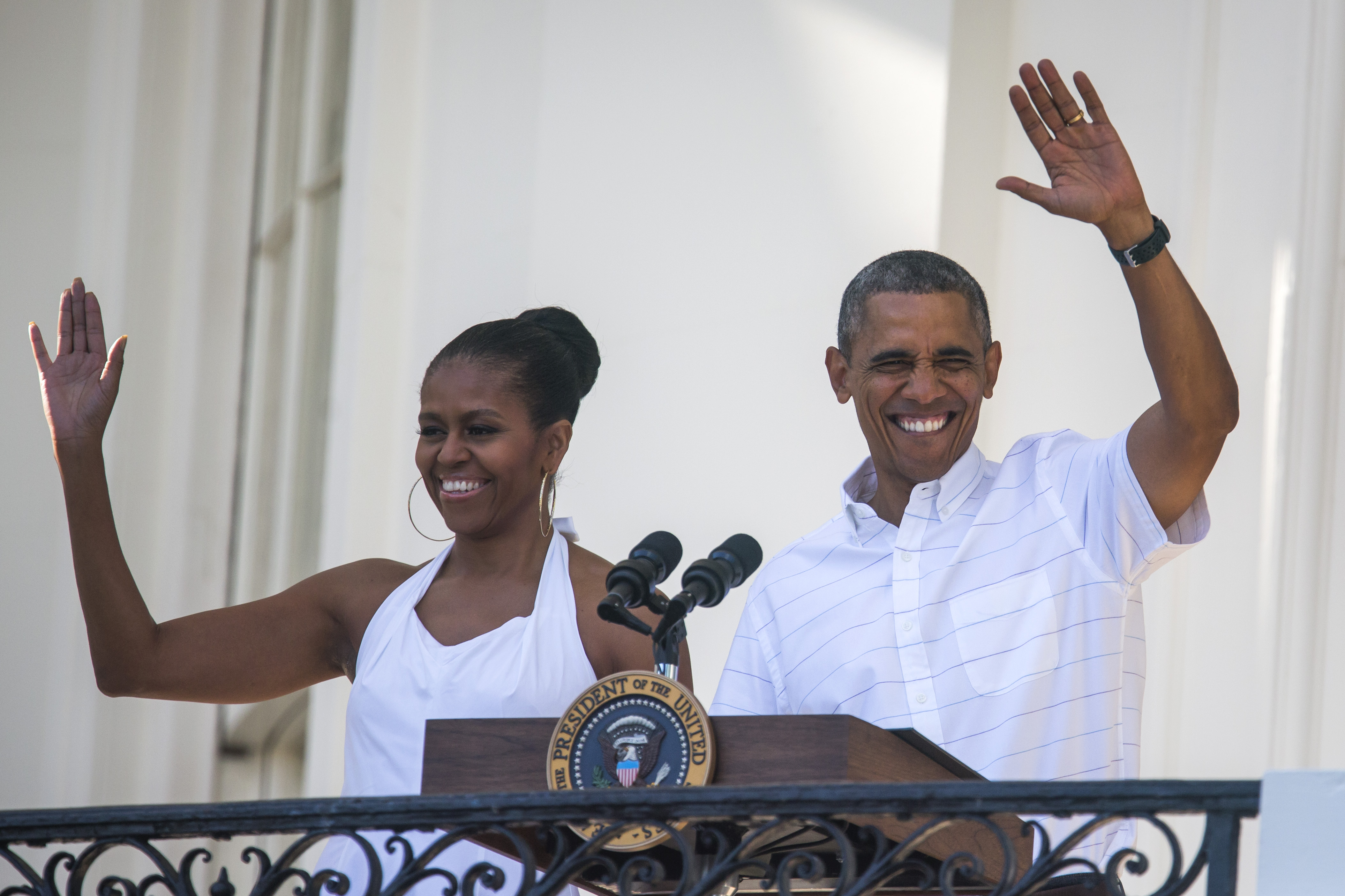 U.S. President Barack Obama and first lady Michelle Obama wave from the South Portico to U.S. veterans and their families, as well as White House staff, during an Independence Day barbecue on the South Lawn of the White House on on July 4, 2014, in Washington, D.C. (Photo by Jim Lo Scalzo-Pool/Getty Images)