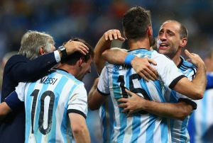 Lionel Messi, Martin Demichelis and Pablo Zabaleta of Argentina celebrate after defeating the Netherlands in a penalty shootout during the 2014 FIFA World Cup Brazil semifinal match between the Netherlands and Argentina at Arena de Sao Paulo on July 9, 2014, in Sao Paulo, Brazil. (Credit: Ronald Martinez/Getty Images)