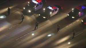 Officers use flashlights to perform a grid search on the 91 Freeway looking for evidence in a Deadly shooting. (Credit: KTLA)