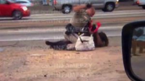 Video shot July 1, 2014, by a motorist showed a CHP officer throw a woman to the ground, straddle her body and repeatedly punch her. (Credit: David Diaz)
