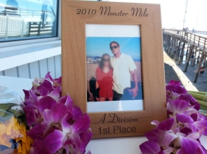 Flowers and photos were left in memory of Ben Carlson at the Newport Beach lifeguard station on July 7, 2014, a day after he died following a rescue. He is shown in a photo with an unidentified woman, whose face has been blurred. (Credit: Chip Yost/KTLA)