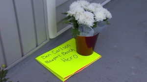 Flowers and cards were left outside a City of Newport Beach office after lifeguard Ben Carlson died while on duty on July 6, 2014. (Credit: KTLA)