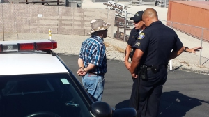 Police handcuffed a man during protests in Murrieta on July 4, 2014. It was not immediately clear if he was arrested. (Credit: KTLA)