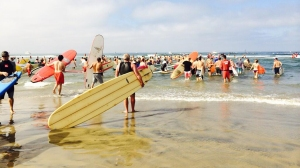 Paddle boarders enter the water for a memorial paddle out held in fallen Newport Beach lifeguard Ben Carlson's honor. (Credit: Sara Welch/KTLA)