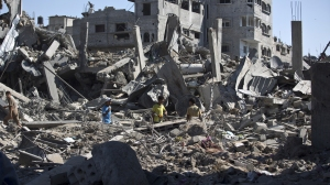 Palestinians walk amid the rubble of destroyed buildings and homes in the Shejaiya residential district of Gaza City on Saturday, July 26, 2014, as families returned to find their homes ground into rubble by relentless Israeli tank fire and air strikes. The death toll in Gaza soared to more than 1,000 as bodies were pulled from the rubble during a 12-hour truce top diplomats urged Israel and Hamas to extend. AFP PHOTO/MAHMUD HAMS (Credit: Mahmud Hams/AFP/Getty Images)