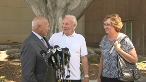 Stow family attorney Tom Girardi talks to media alongside David and Ann Stow after the verdict was delivered on July 9, 2014. (Credit: KTLA)
