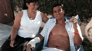 Steve Robles recovered at his Lomita home with his wife, Glenda Robles (left), after he was attacked by a shark on July 5, 2014. (Credit: KTLA)