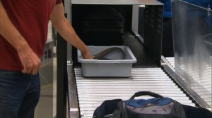 Travelers place items in a bin before passing them through an X-ray machine at a TSA security checkpoint prior to flying. (Credit: CNN)