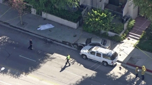 A crash in the San Fernando Valley involving a cyclist and two vehicles left one person dead on July 17, 2014. (Credit: KTLA)