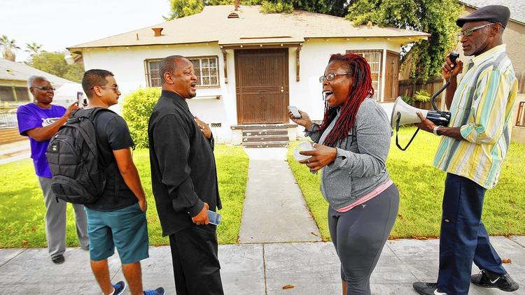 Community activist Najee Ali, center left, exchanges words with Jasmyne Cannick, center right, outside the home of Compton school board member Skyy Fisher following his arrest. Cannick is a spokeswoman for Fisher, while Ali wants him to resign. (Credit: Al Seib/Los Angeles Times)