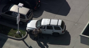 Deputies stood next to an SUV at a gas station in Moreno Valley that appeared to be a crime scene on July 22, 2014. (Credit: KTLA)