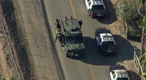 A SWAT vehicle and patrol cars were on scene at search for one or two people in Moreno Valley on July 22, 2014. (Credit: KTLA)