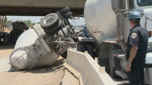 The truck, carrying sand, was launched on the K-rail and then collided with a support beam on the 215 Freeway on July 15, 2014. (Credit: KTLA)