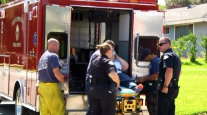 Paramedics prepare to place a woman in an ambulance after she was attacked at a home in West Covina on Sunday, July 6, 2014. (Credit: Flying Lion TV)