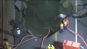 Crews gaze into massive hole created by ruptured water main on Sunset Blvd. in Westwood. (Credit: KTLA)