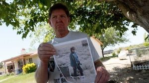 Ben Devitt holds a photo of his wife, Pamela Maria Devitt, who was killed by a pack of pit bulls on May 9, 2013, in Littlerock. (Credit: Irfan Khan / Los Angeles Times)